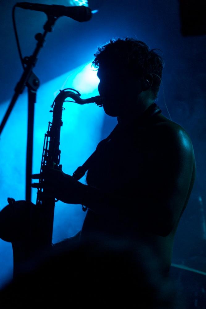 Concert au cabaret sauvage à Paris : Saxophoniste en ombre chinoise sur fond bleu