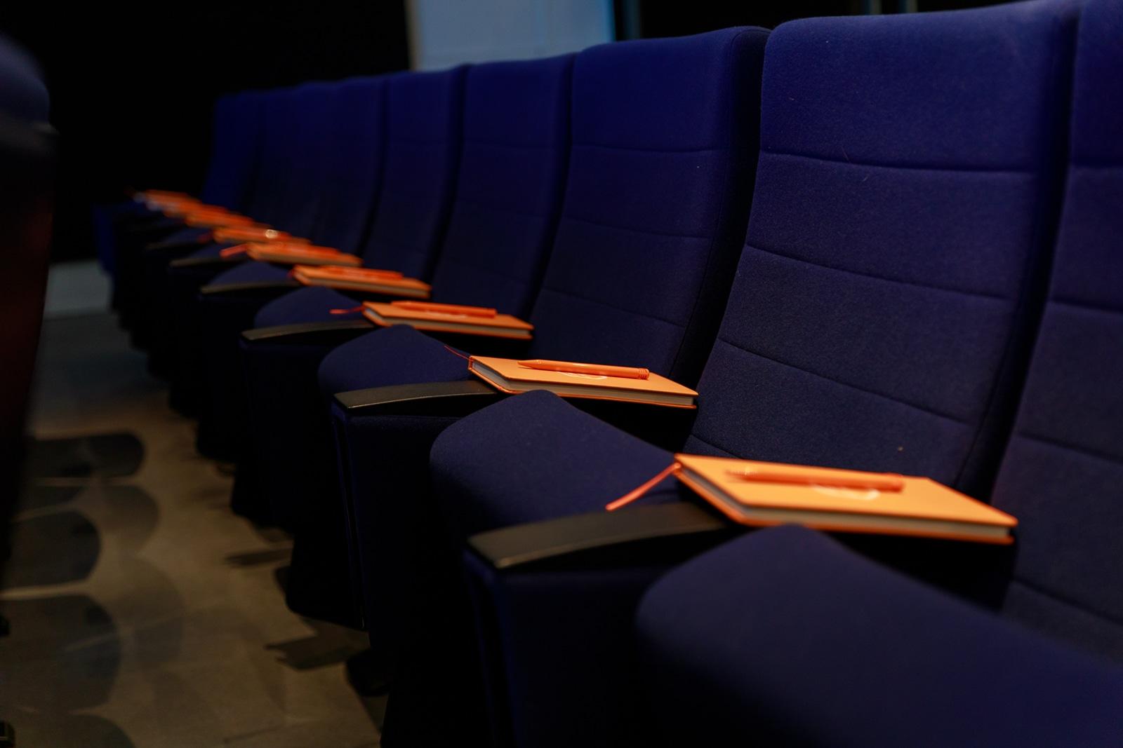 Fauteuils d'un auditorium avec des carnets oranges sur les accoudoirs