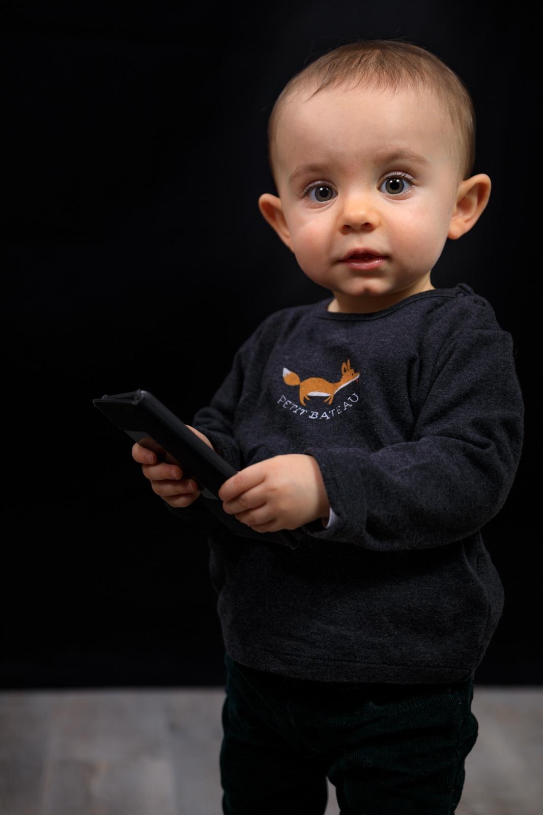 Petit garçon de 18 mois avec un téléphone style homme d'affaire