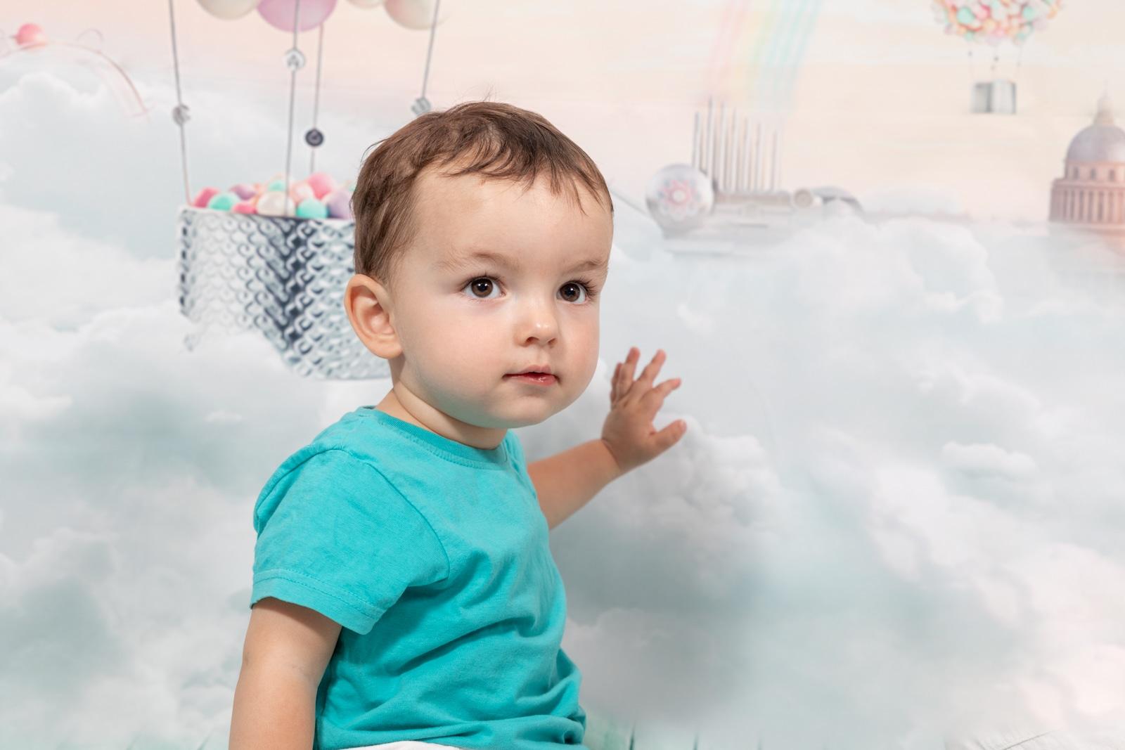 Petit garçon devant un fond de ciel avec des ballons