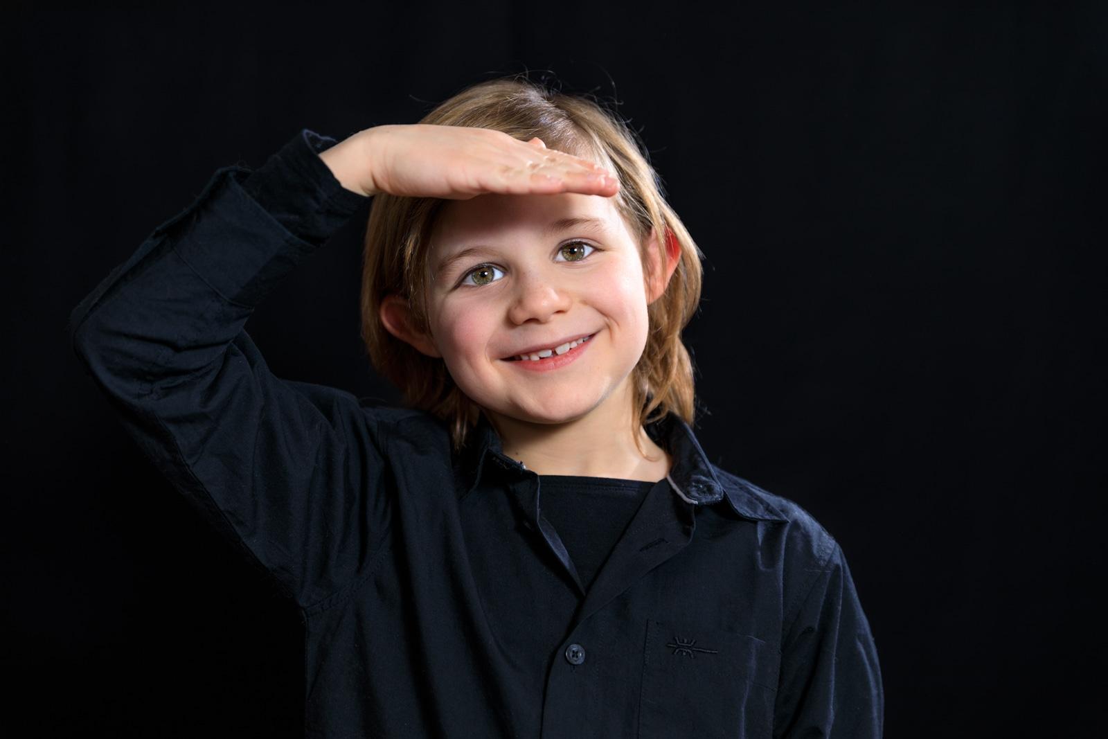jeune garçon souriant et posant de face