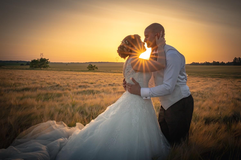 Mariés s'embrassant dans le soleil couchant