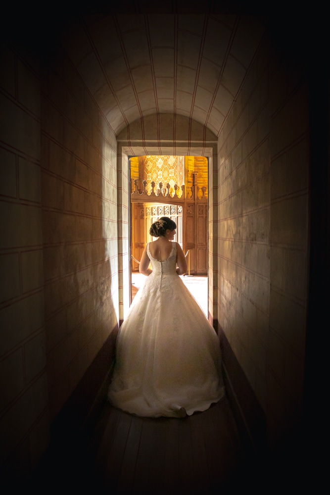 Mariée de dos dans un couloir du Château de Pierrefond dans l'Oise