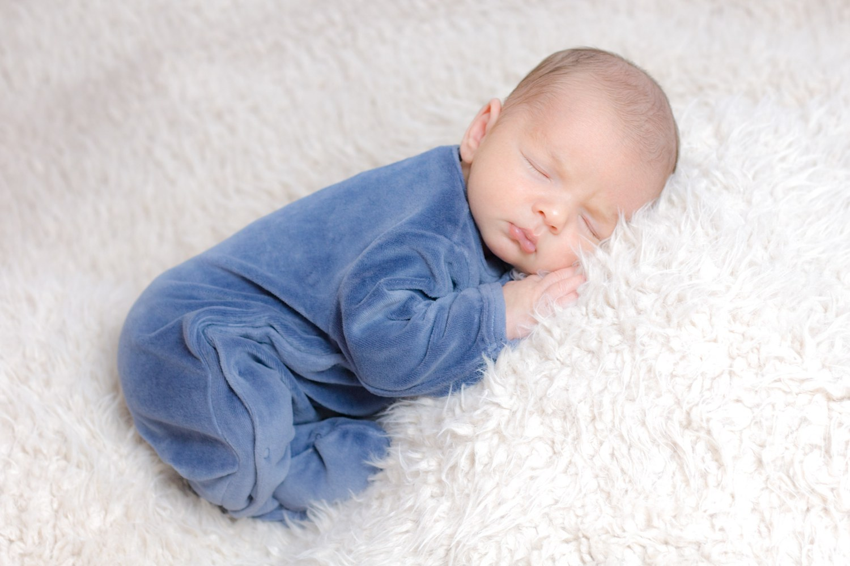 Bébé habillé dormant sur fausse fourrure